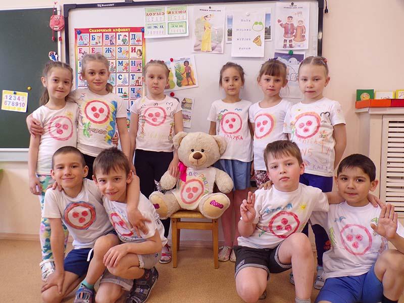 Дети под руководством воспитателя с помощью трафарета и восковых мелков нанесли орнамент Знамени Мира на футболки