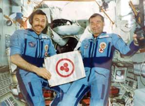 Космонавты А.Н. Баландин и Г.М. Стрекалов со Знаменем Мира на борту орбитального пилотируемого комплекса «Мир». Август 1990 г.